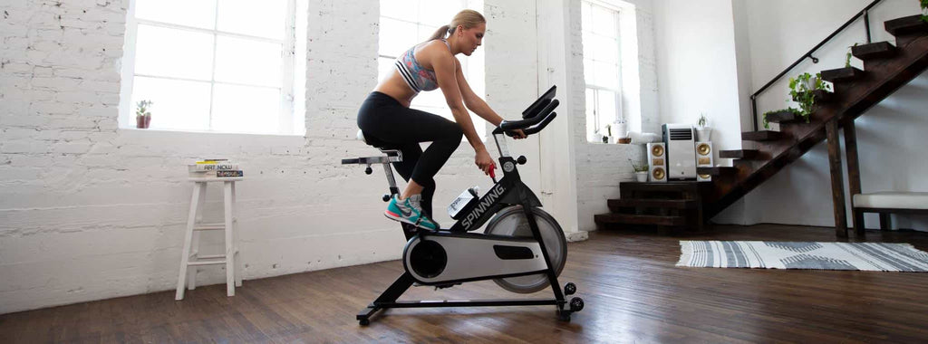 Woman using a Spinning bike at home