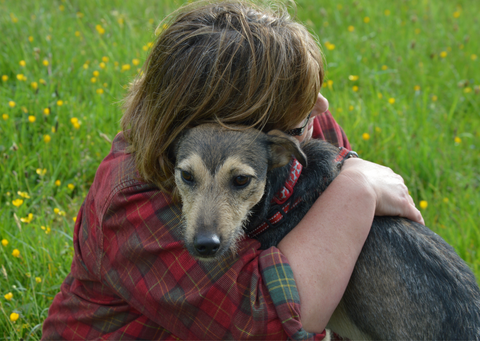 Another lady hugging her dog in a field.