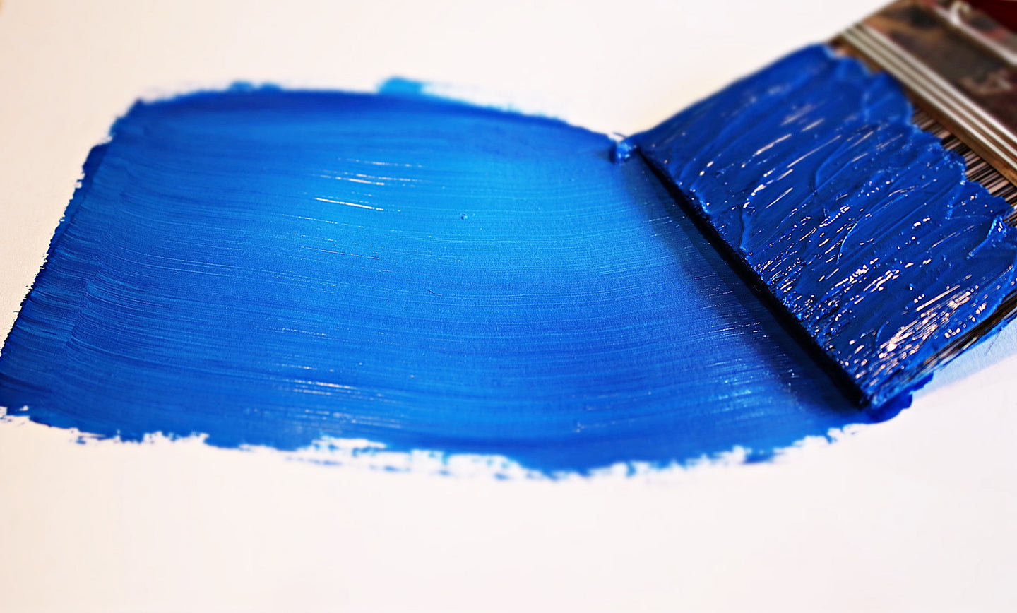Image of paint brush making a brush stroke of blue paint