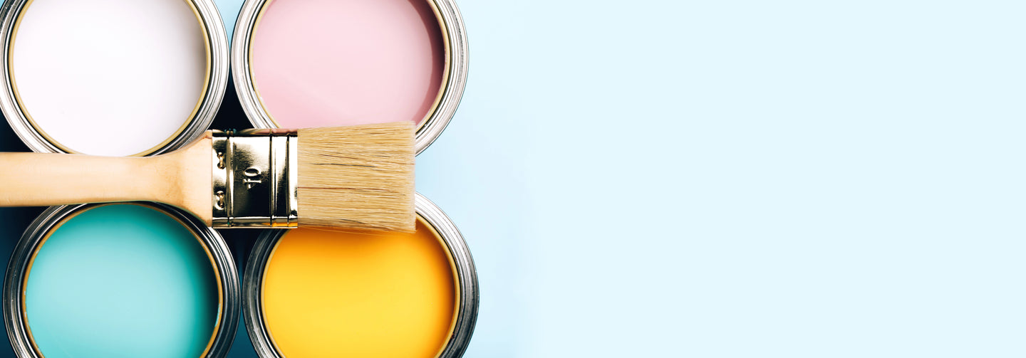 Image of paintbrush on top of 4 colourful cans of interior paint