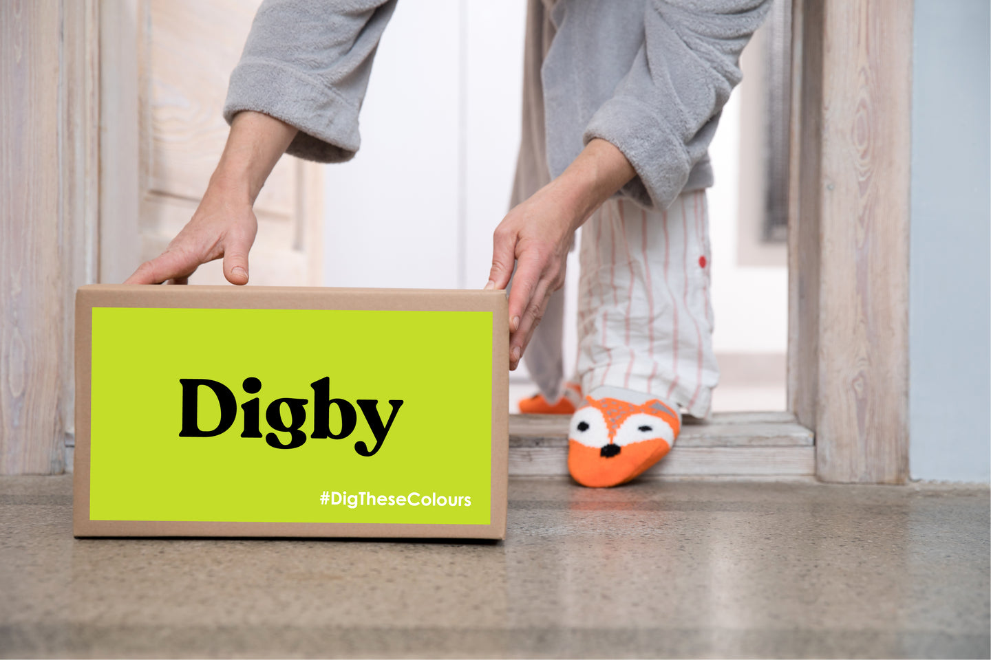 Image of woman picking up a Digby Paints box at her front door with slippers on