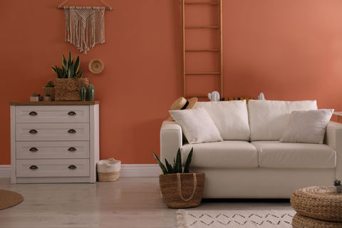 Burnt sienna painted living room with wicker accents and cream coloured couch