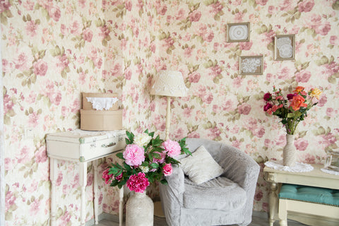 Dramatic floral wallpaper provides a background to muted seating area, accented with fresh flowers