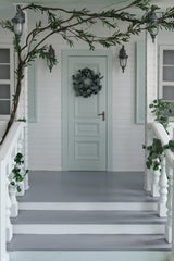Front porch decorated simply for the holidays with greenery