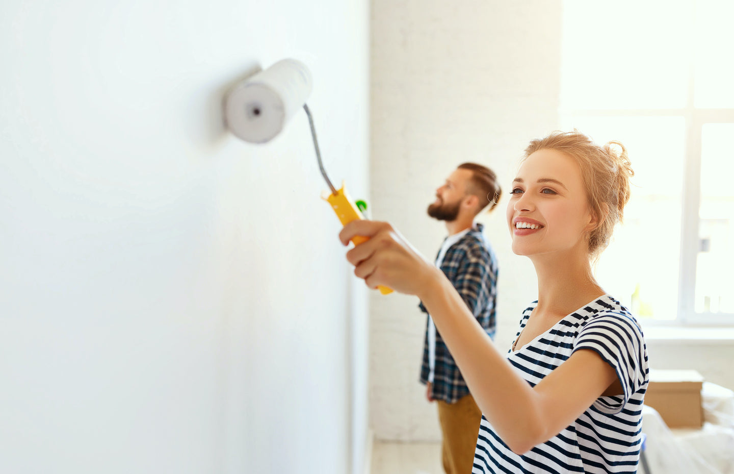 image of happy woman painting her home with Digby Paints