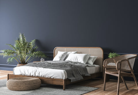 Navy Bedroom With Wicker Bed Frame and Side Table