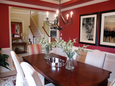 Vibrant red dining room with rich wooden table and cream panel accents