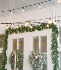 Holiday wreath and garland with Edison bulb lights for the holidays