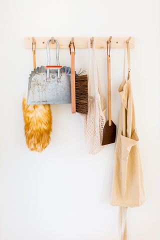 Hooks with dustpan, brush, apron, and a mesh bag hanging on a white wall