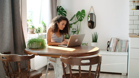 Young woman typing on laptop surrounded by houseplants
