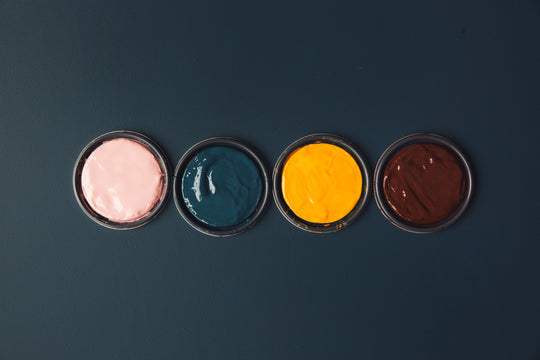 At Digby we've worked hard to create a palette of colours you'll love. This image is of 4 paint lids covered in paint against a dark backdrop. Buy interior home paints online.