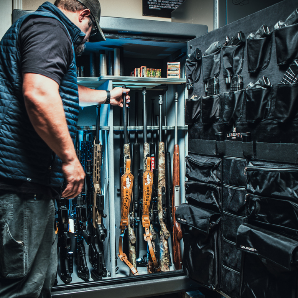 safe open with man looking at guns inside