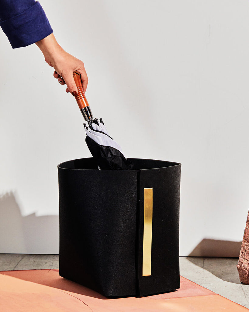 Black rubber and brass bin with hand holding umbrella on terracotta surface.