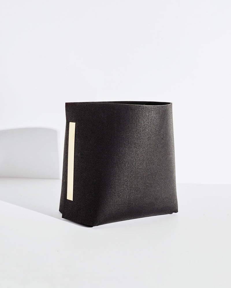 Black rubber and brass bin on white background.