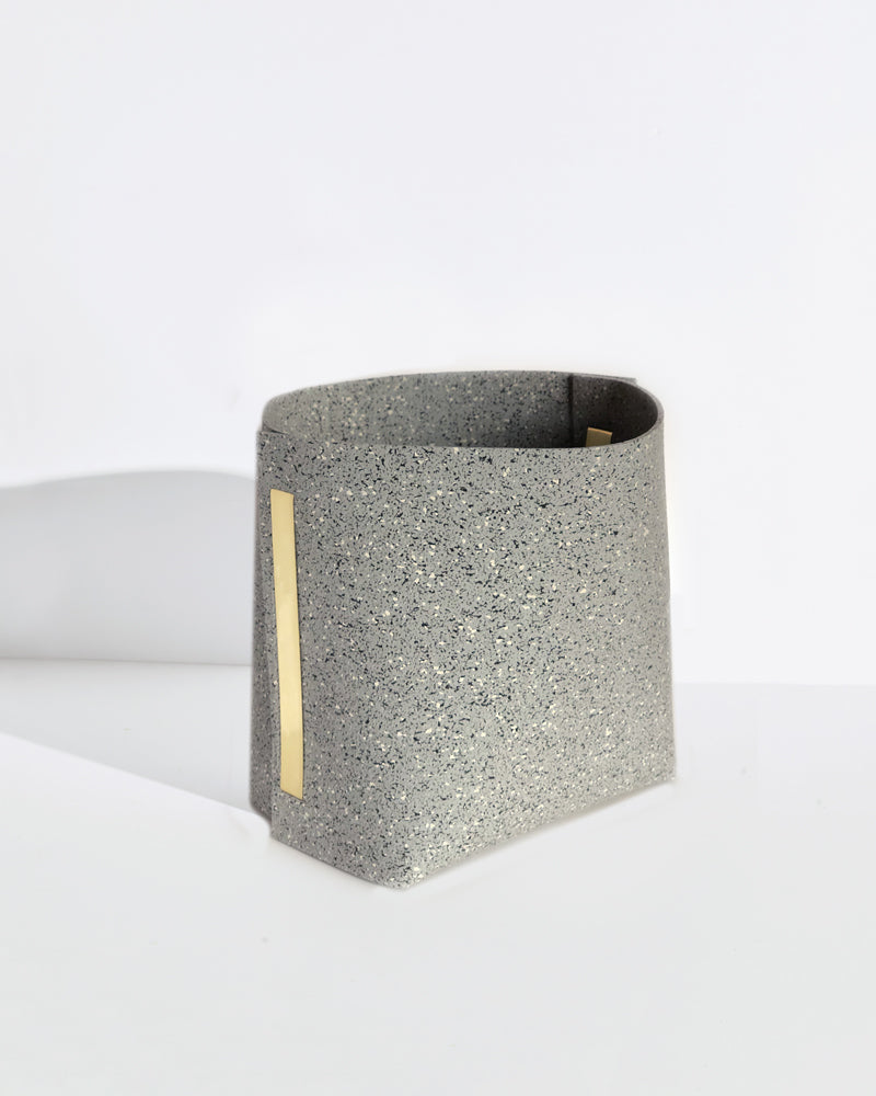Speckled grey rubber and brass bin on white background.