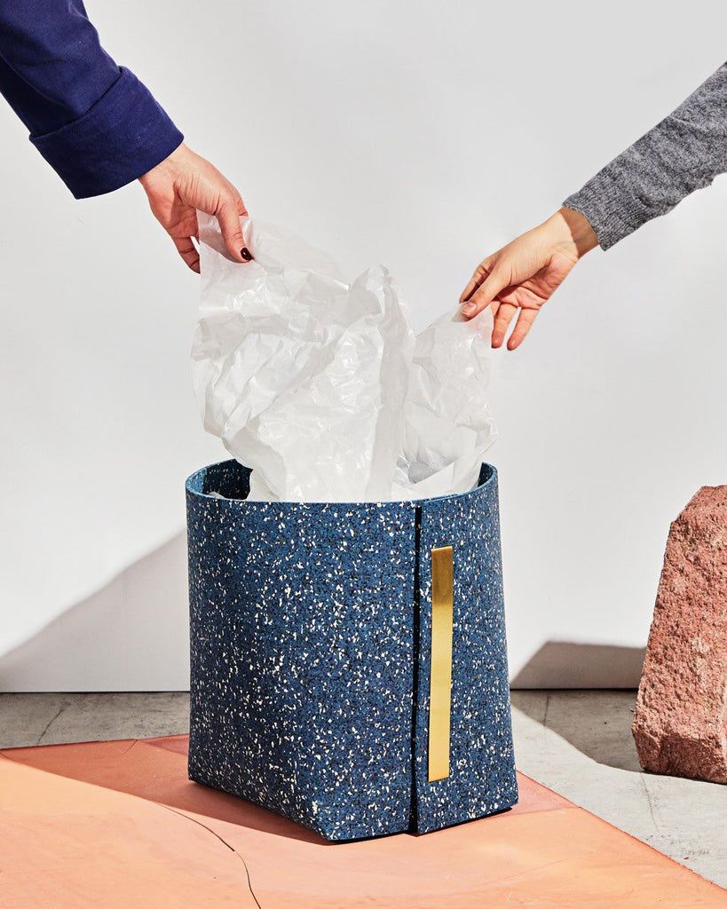 Speckled blue rubber and brass bin with hands pulling white crumbled paper on terracotta surface.