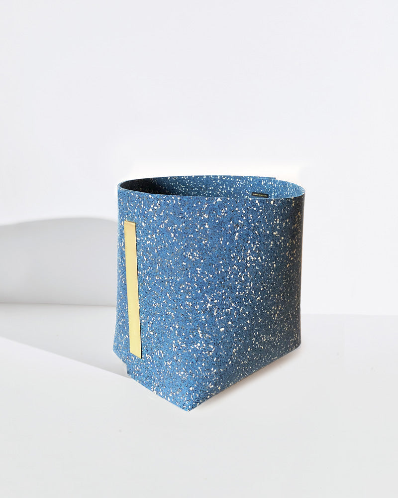 Speckled blue rubber and brass bin on white background.