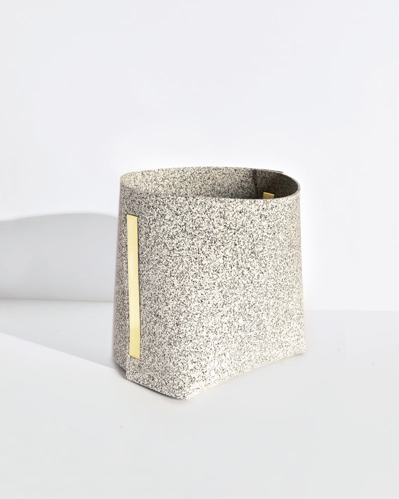Speckled beige rubber and brass bin on white background.