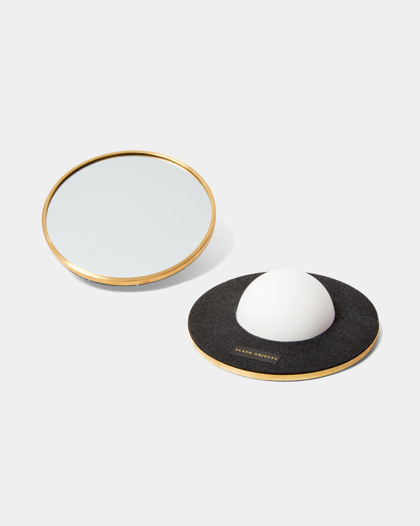 Two round mirrors with brass frame. One of the mirrors is faced downward, with a white half sphere base and black rubber on its back.
