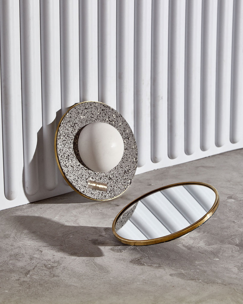 Two round mirrors with brass frame and half sphere base. One mirror balancing on concrete surface. Other mirror balanced against wall revealing speckled grey rubber back.