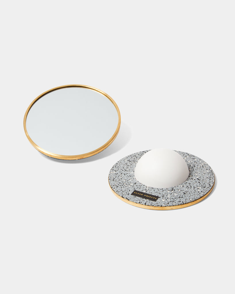 Two round mirrors with brass frame. One of the mirrors is faced downward, with a white half sphere base and speckled grey rubber on its back.