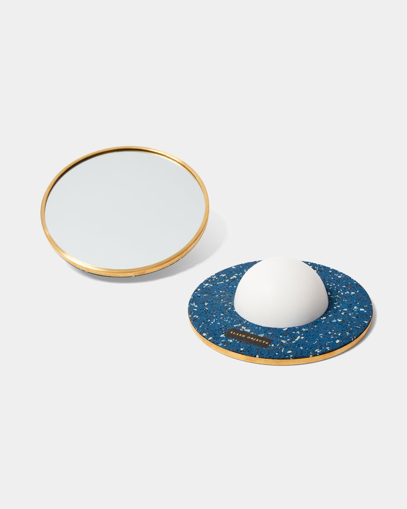 Two round mirrors with brass frame. One of the mirrors is faced downward, with a white half sphere base and speckled blue rubber on its back.