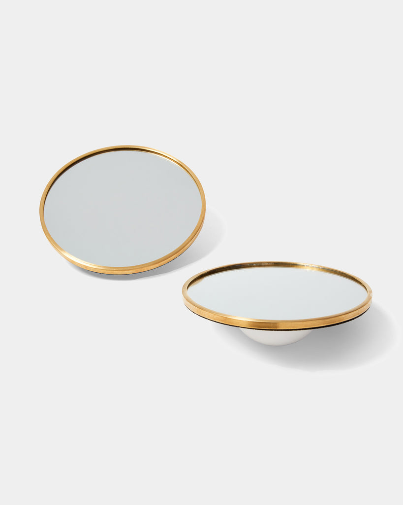 Two round mirrors with brass frame and half sphere white ceramic base.