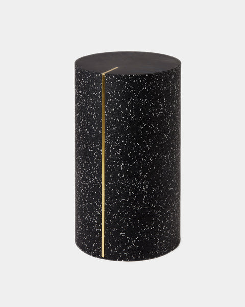 Round side table with speckled black rubber, brass strip and black concrete table top.