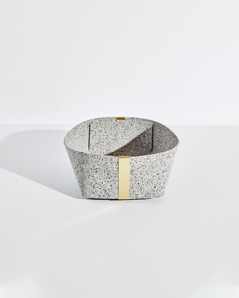 Large speckled grey rubber and brass basket on white background.