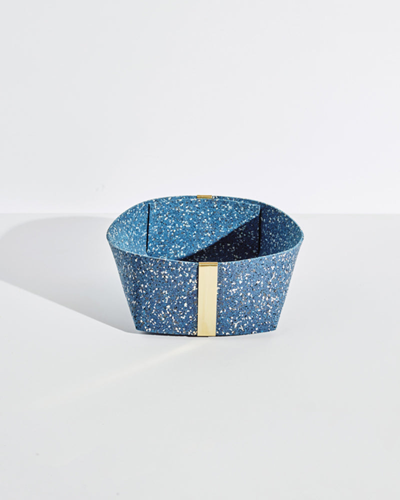 Large speckled blue rubber and brass basket on white background.