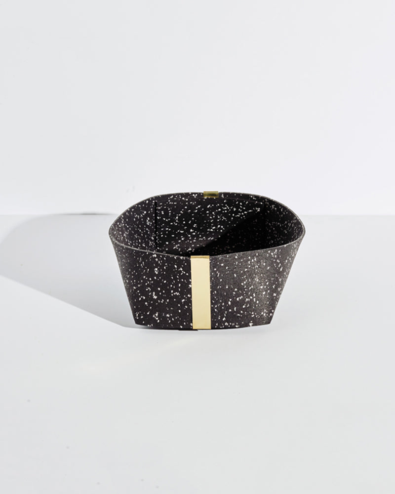 Large speckled black rubber and brass basket on white background.