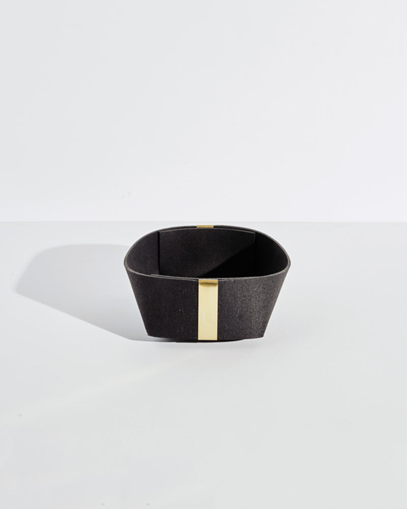 Medium black rubber and brass basket on white background.