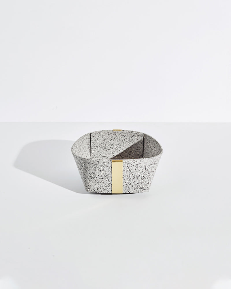 Medium speckled grey rubber and brass basket on white background.