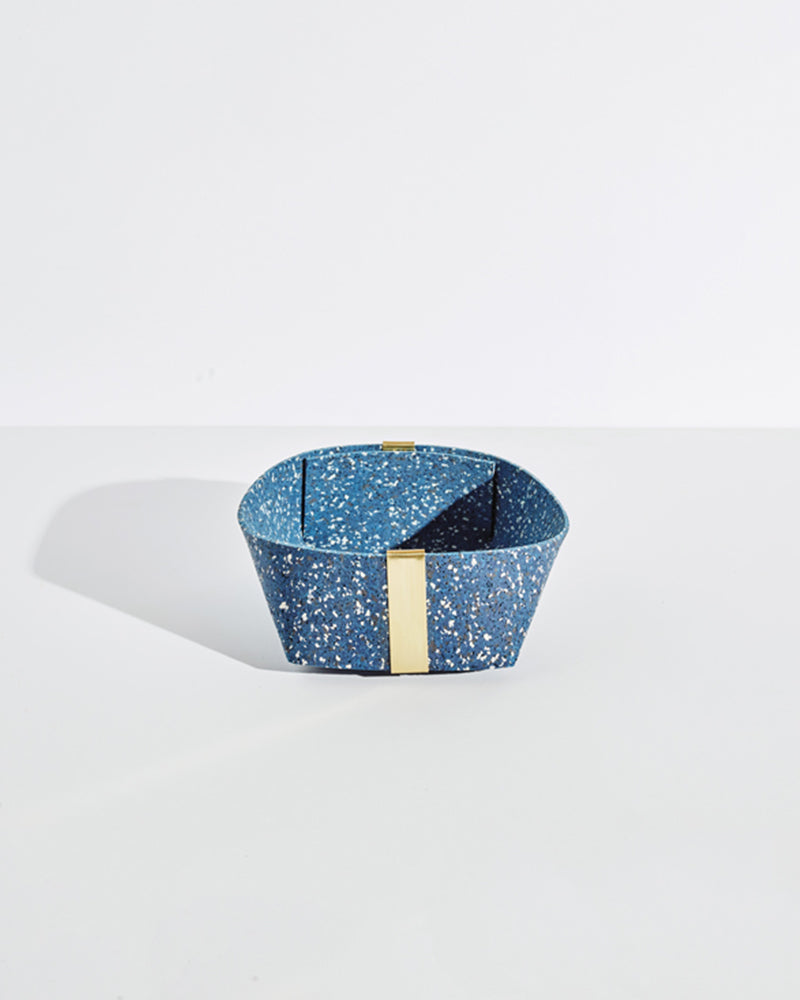 Medium speckled blue rubber and brass basket on white background.