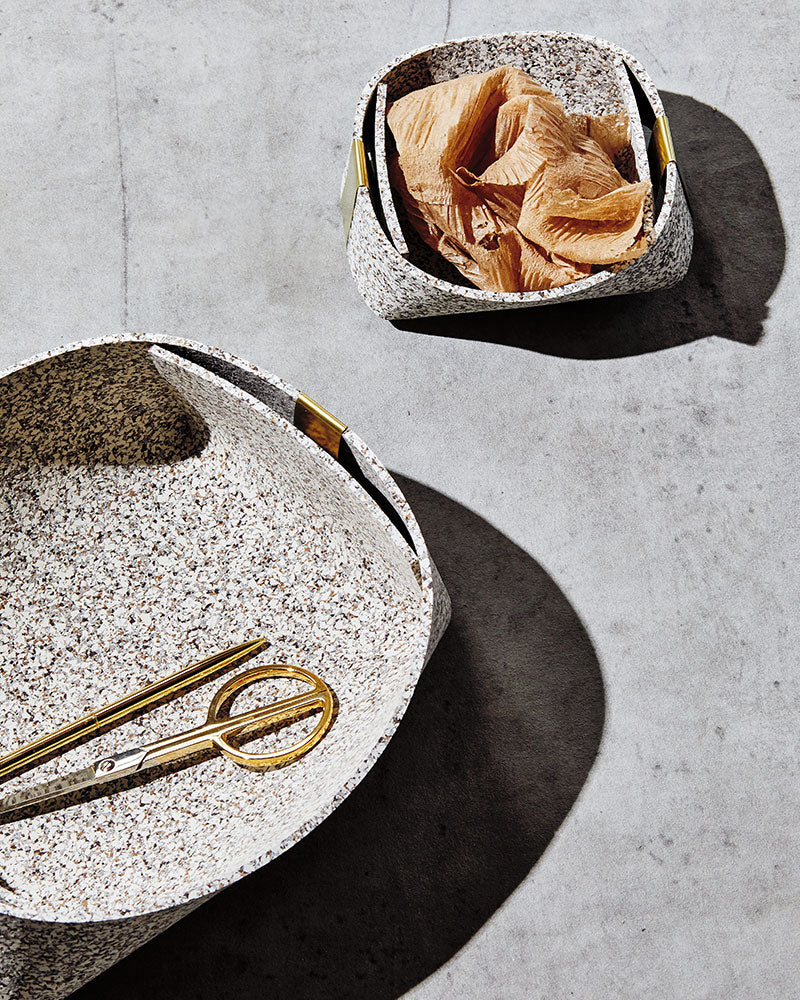 Two speckled beige rubber and brass baskets on concrete surface. One basket has brass scissors and the other has brown paper inside.
