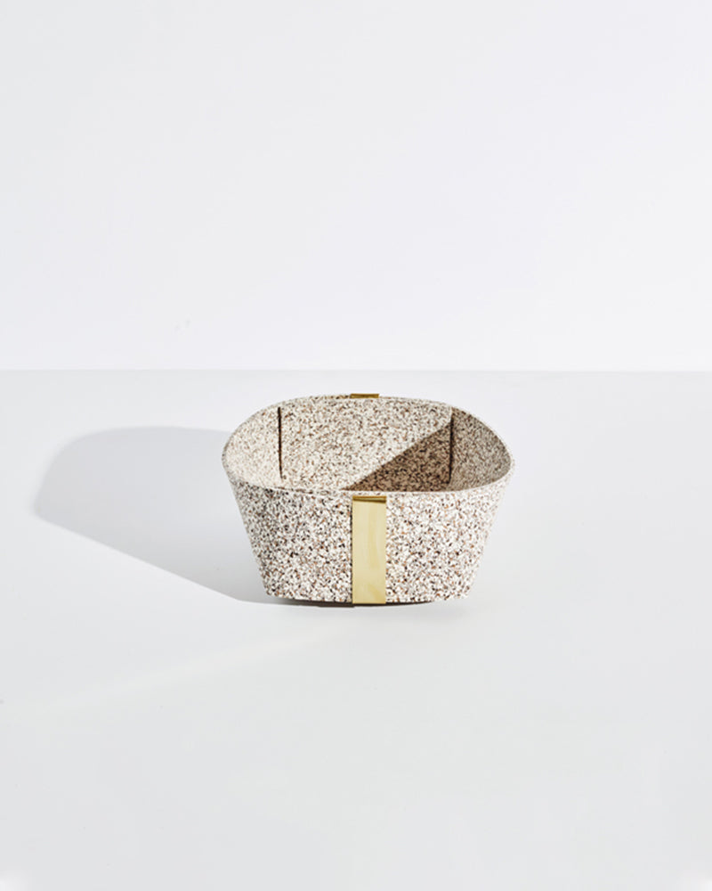 Medium speckled beige rubber and brass basket on white background.
