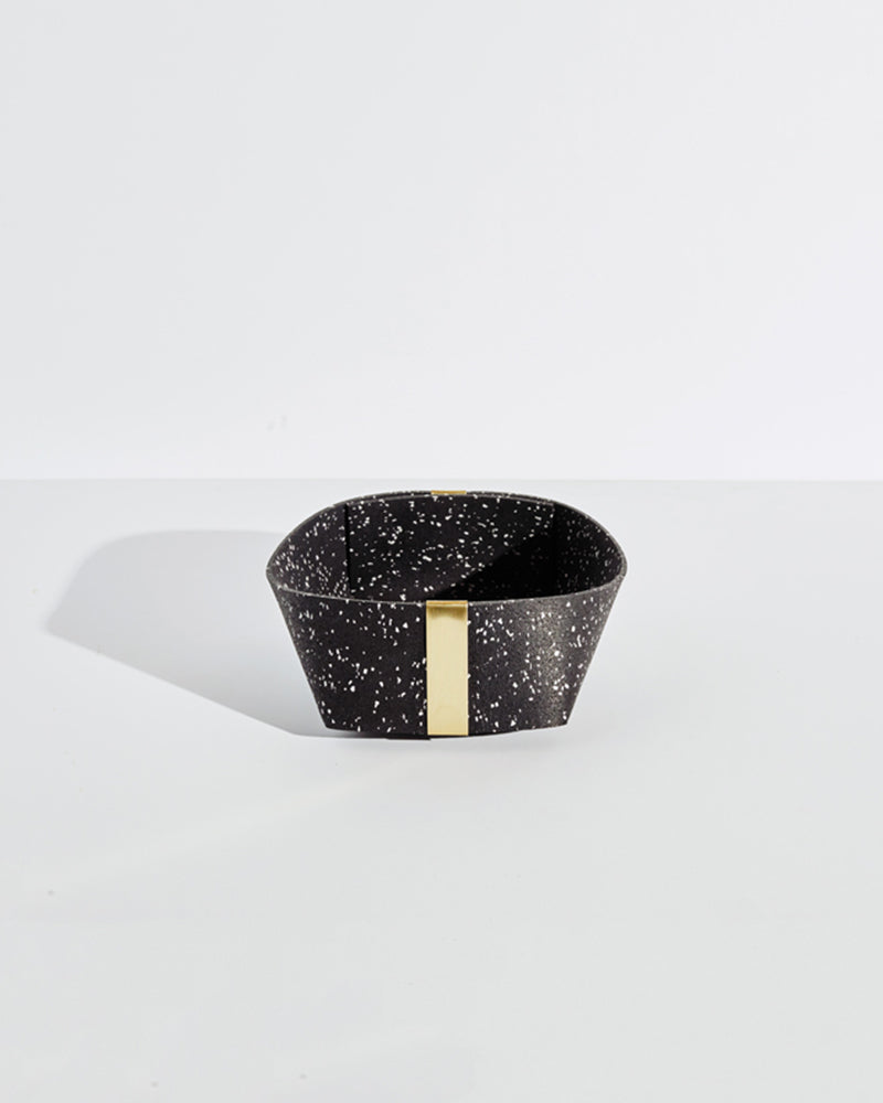 Medium speckled black rubber and brass basket on white background.