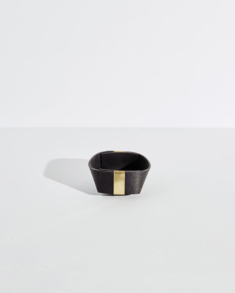 Small black rubber and brass basket on white background.