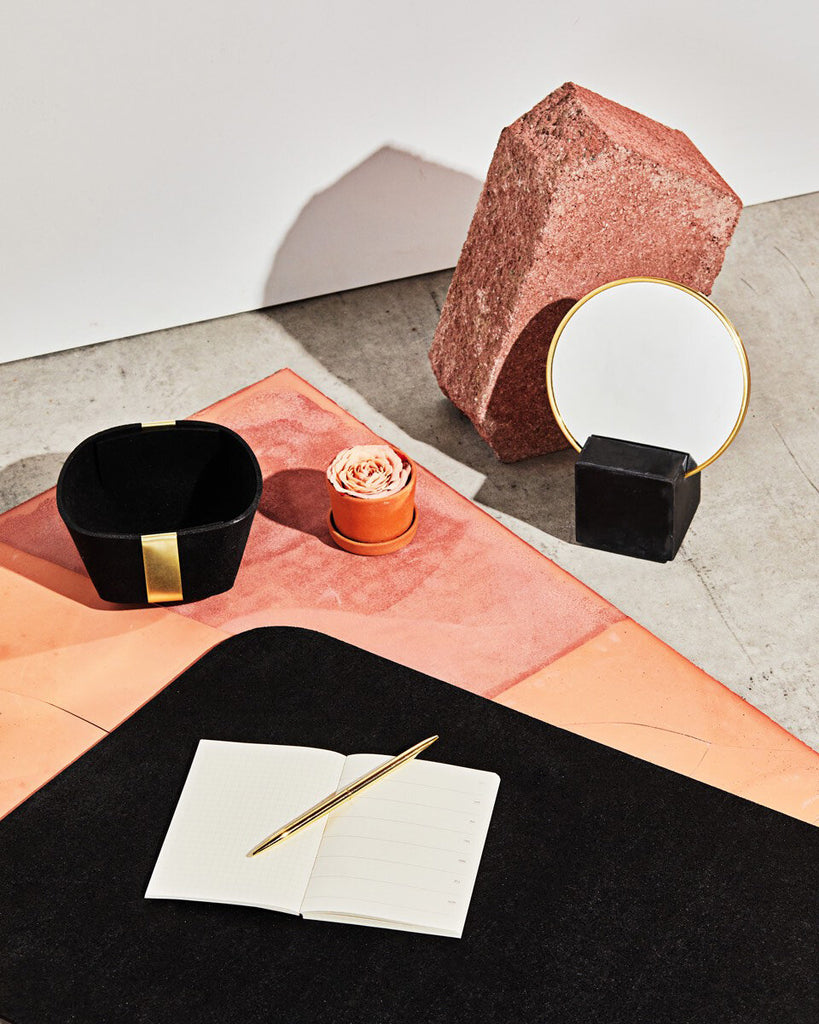 Desk set up with black cube base vanity mirror, small black rubber & brass basket and rounded edge black rubber desk mat with open notebook and brass pen on concrete ground with terracotta surface.