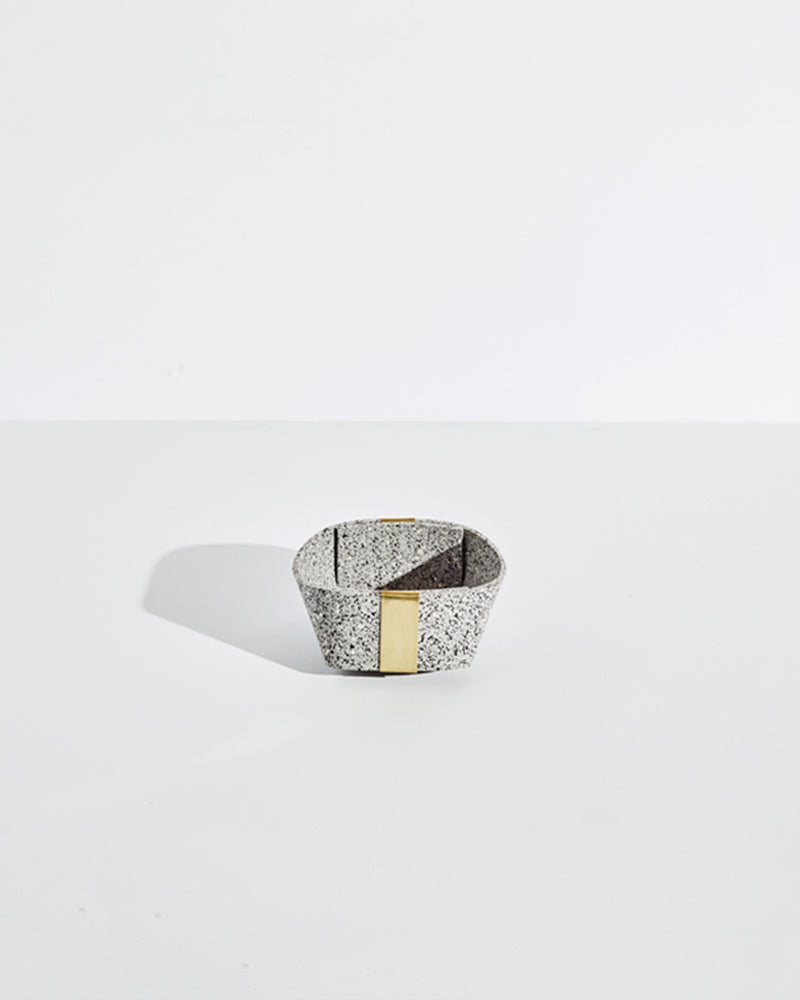 Small speckled grey rubber and brass basket on white background.