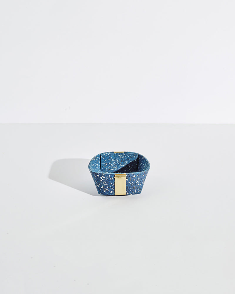 Small speckled blue rubber and brass basket on white background.