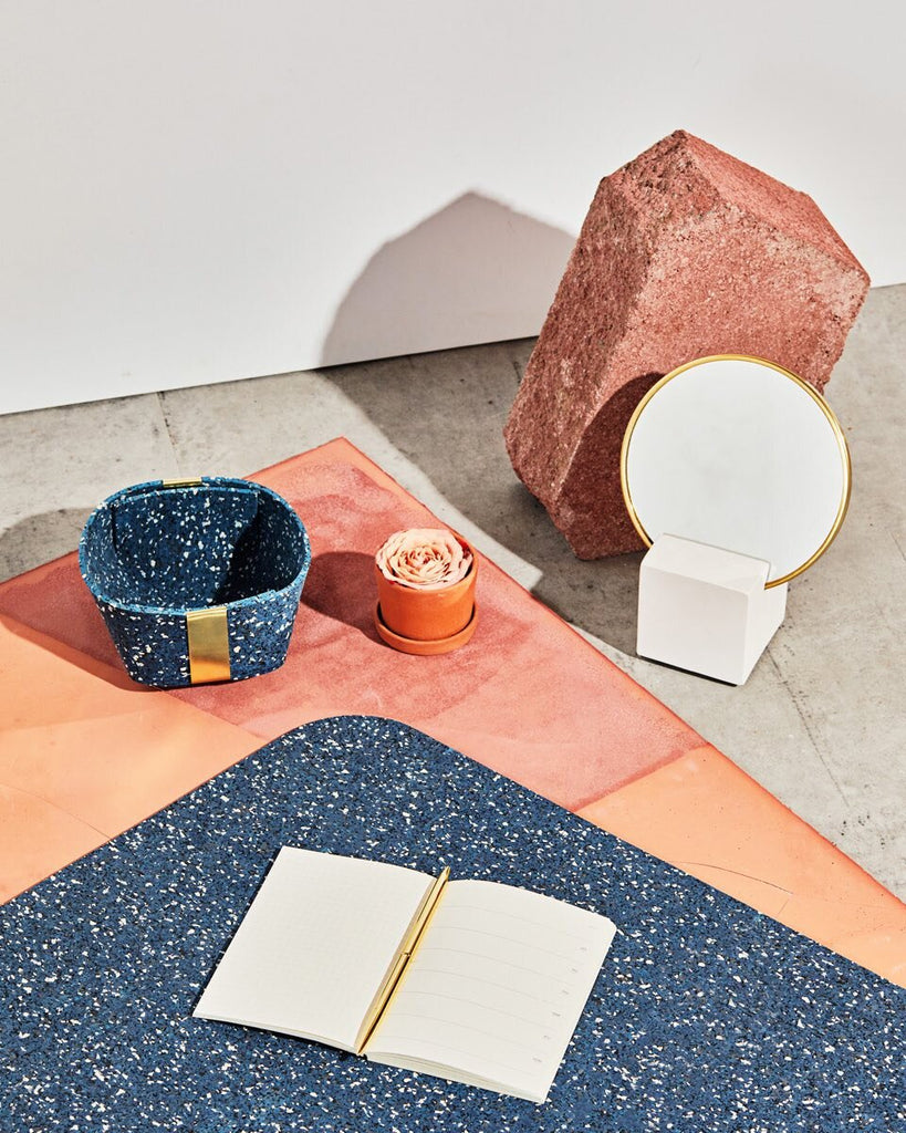 Desk set up with white cube base vanity mirror, small speckled blue rubber & brass basket and  rounded edge speckled blue rubber desk mat with open notebook and brass pen on concrete ground with terracotta surface.