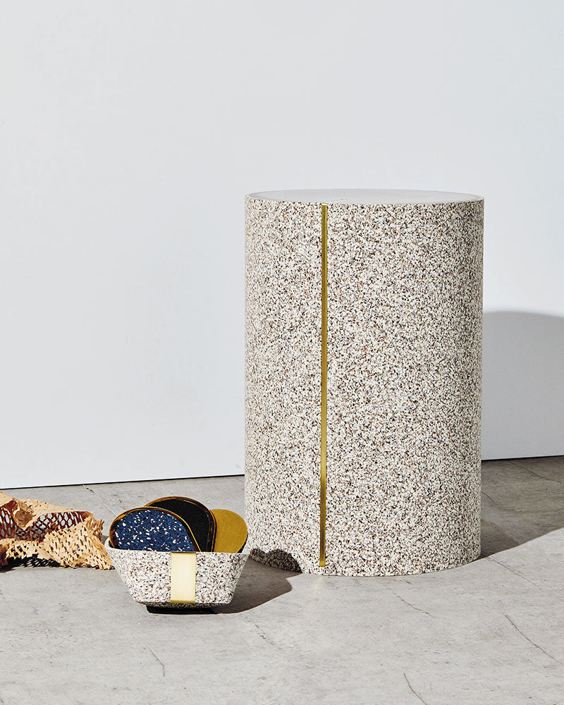 Small speckled beige rubber basket with oval coasters and speckled beige rubber CYL side table on concrete surface.