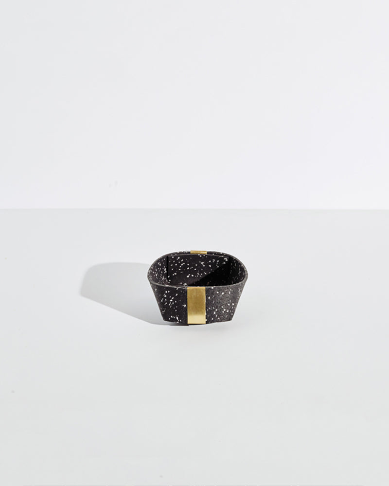 Small speckled black rubber and brass basket on white background.