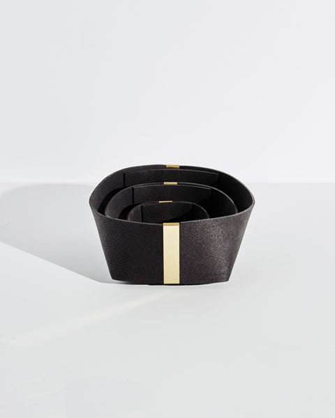 Three black rubber and brass baskets, nested inside one another on white background.
