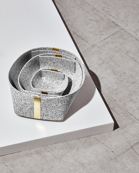 Three speckled grey rubber and brass baskets, nested inside one another on white foam board on concrete surface