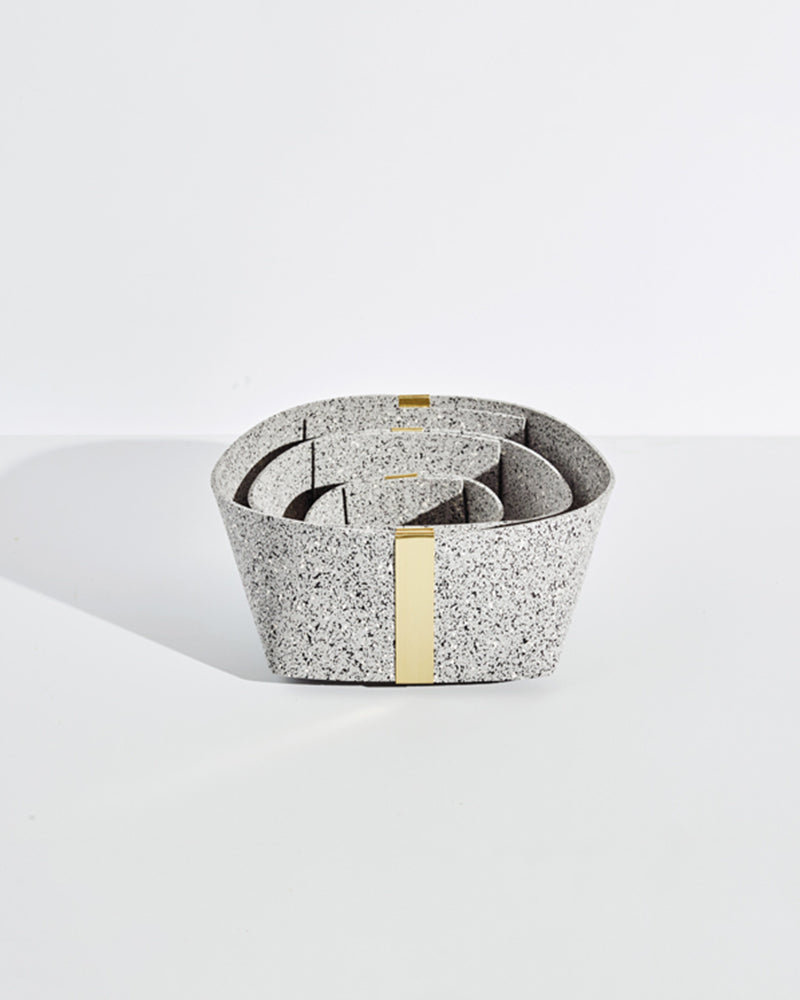 Three speckled grey rubber and brass baskets, nested inside one another on white background.