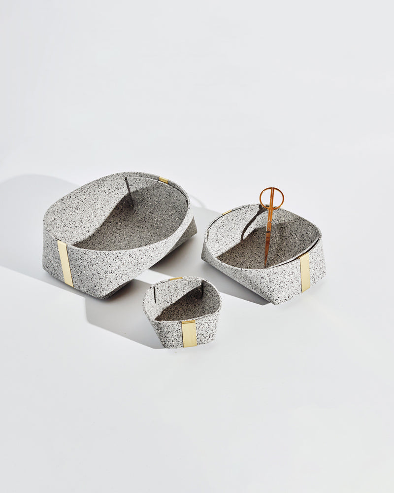 Three speckled grey rubber and brass baskets on white background. One basket has brass scissors inside.