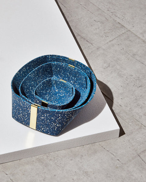 Three speckled blue rubber and brass baskets, nested inside one another on white foam board on concrete surface