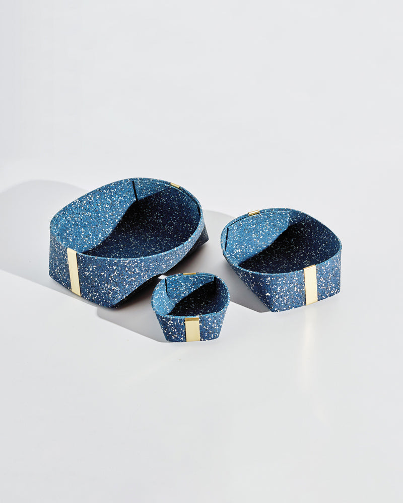 Three speckled blue rubber and brass baskets on white background.